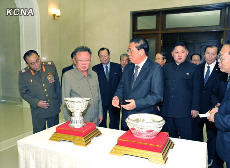 Choummaly Sayasone präsentiert Kim Jong Il und Kim Jong Un seine Geschenke